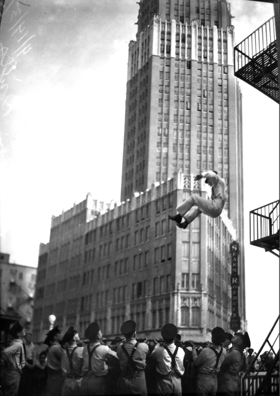 San Antonio firefighters practicing catching high rise rescues at the old central firehouse with Smith Young Building in the background.  Note Sears & Roebuck sign. | Drink up the history with The Barwalk, San Antonio TX